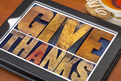 Give thanks - Thanksgiving concept. Text in vintage letterpress printing blocks on a digital tablet with cup of tea and cookie stock photos