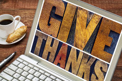 Give thanks - Thanksgiving concept. Text in vintage letterpress printing blocks on a laptop screen with a cup of coffee royalty free stock image