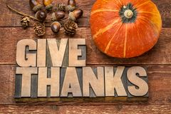 Give thanks - Thanksgiving concept. Word abstract in letterpress wood type printing blocks with winter squash and acorn decoration stock image