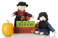 Give Thanks. Two old faceless pilgrim dolls by a Give Thanks sign topped by a turkey. On a white background stock image