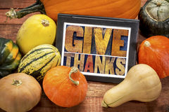 Give thanks word abstract on digital tablet. Give thanks word abstract in letterpress wood type on a digital tablet surrounded by pumpkin and winter squash stock image