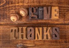 Give Thanks Text on a Wooden Background. Give Thanks written with wooden block lettering on a rustic wooden background stock image
