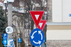 Give way and roundabout traffic signs. In a small busy town Stock Photo