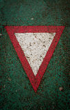 Give Way Sign. Red triangle representing give way sign painted on green asphalt Stock Photos