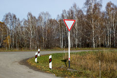 Give a way sign. Against autumn forest Stock Photos