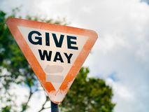 Give way sign on a suburban road under overcast skies in the Sey Royalty Free Stock Image