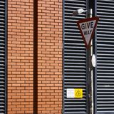 Give way street sign on pole. Priority street sign on the roads of Belfast against red brick wall stock photo