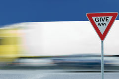 Give way text yield road traffic sign, motion blurred truck, white tent background, blue summer sky Stock Photography