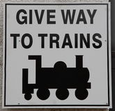 Give Way to Trains Sign. A square white sign with black writing warning 'Give Way To Trains' with a picture of a train below royalty free stock photography