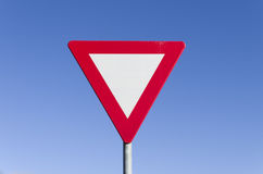 Give way traffic sign. Against a clear blue sky Stock Images