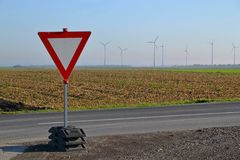 Give way traffic sign. With wind mills and field in background Royalty Free Stock Images