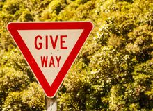 Give Way Triangular Shaped street traffic sign on the rural road area in the nature of New Zealand scenic driving range.  Stock Photos