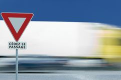Give way yield french cédez le passage road sign, motion blurred truck vehicle traffic background, white signage triangle red. Frame regulatory warning stock images