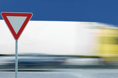 Give way yield road traffic sign, motion blurred truck background, blue sky Stock Photo