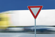 Give way yield traffic sign and truck. Give way yield road traffic sign and truck in the background stock images