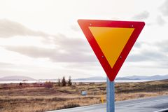 Give Yield Warning Road Sign in Iceland. Red and Yellow Give Yield Traffic Sign in the Countryside of Iceland on a Cloudy Autumn Day royalty free stock photo