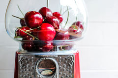 Give Your Kids Something Sweet. Antique bubblegum machine filled with fresh, red cherries Stock Photo