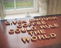 Given enough coffee could rule the world. Quote made with the block wooden letters over the table, next to a cup of coffee, composition with tone image royalty free stock images