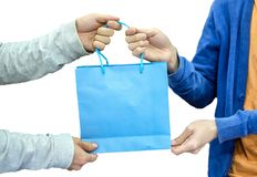 Giver hand holding blue paper bag with receiver. On white background Royalty Free Stock Image