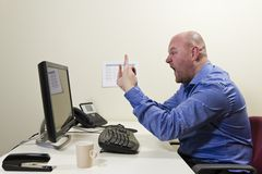 Gives Finger to the Computer. Angry worker give finger to his computer stock image