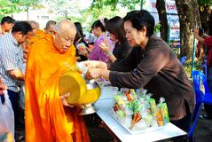 Gives food to a monk. LAMPHUN , THAILAND April 24 : An unidentified woman Gives food to a monk.Thai traditional, people will make merit making by give food to Royalty Free Stock Image