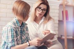 Givign femminile dello psicologo di Professioanl una prova ad uno scolaro fotografie stock