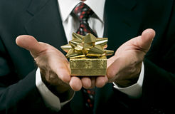 Giving. Close up of a man in a suit giving a gift Royalty Free Stock Image