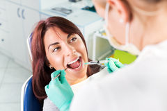 Giving anesthesia to the patient before dental surgery. Young female dentist giving anesthesia to the patient before dental surgery. Selective focus, focus on Stock Image