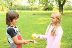 Giving an apple. Kids - smiling blond girl giving an apple to a boy Stock Photo