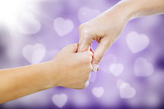 Giving assistance on purple defocused lights. Hand gestures of a mother giving her hand to her child on purple love shape defocused lights Royalty Free Stock Image
