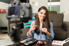 Giving beauty advice on a video blog. Pretty young brunette talking about makeup brushes on video for her beauty blog online royalty free stock photo