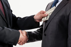 Giving a bribe into a pocket. Closeup shot Royalty Free Stock Photography