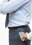Giving a bribe into a pocket Stock Image