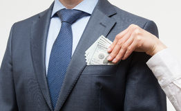 Giving a bribe into a pocket Stock Images