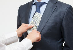 Giving a bribe into a pocket Royalty Free Stock Image
