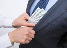 Giving a bribe into a pocket. Closeup shot Royalty Free Stock Photos