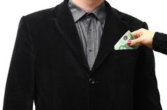Giving a bribe into a suit pocket Royalty Free Stock Photo