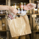 Giving a brown paper bag on a shop with the hands Royalty Free Stock Photo