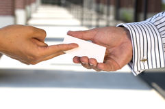 Giving a business card. Woman giving a man a business card Stock Image
