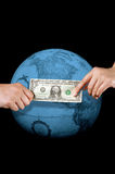 Giving or buying, worldwide. This stock photo shows one hand giving a dollar to the hand of another, in front of a blue tinted globe.  Can illustrate many Royalty Free Stock Photography