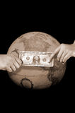 Giving or buying, worldwide. This stock photo shows one hand giving a dollar to the hand of another, in front of a globe.  Can illustrate many concepts including Stock Photography