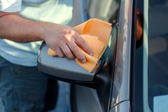 Giving the car a good polish - close up of cleaning car with mic. Rofiber cloth, car detailing Stock Image
