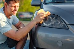Giving the car a good polish - close up of man cleaning car with. Microfiber cloth, car detailing Royalty Free Stock Images