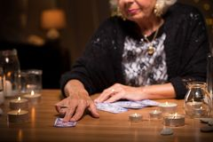 Giving a card. Old fortune teller is giving a card to her client Royalty Free Stock Photography