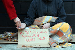 Giving change. Wealthy woman gives change to poor man begging on sidewalk on cold autumn day Royalty Free Stock Image