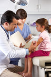 Giving Child Injection In医生医生的办公室 库存图片