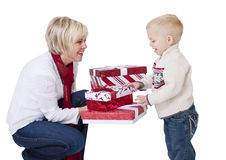 Giving Christmas Presents to a Child. A cute little boy opening christmas presents with his mother. Isolated on a white background Stock Photo