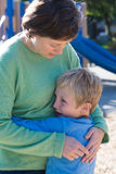 Giving Comfort. A mother consoles her son, perhaps over a playground altercation royalty free stock photos
