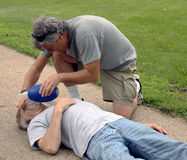 Giving cpr help. Man giving cpr to a man on a sidewalk Royalty Free Stock Images