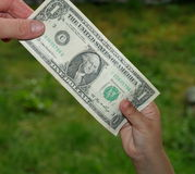 Giving dollar. Giving small child dollar bill stock photography